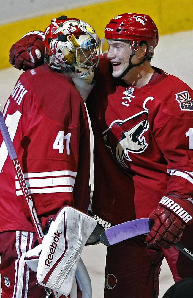 Phoenix Coyotes goalie Mike Smith (41), left, celebrates with Shane Doan (19) after scoring a third period goal during an NHL hockey game against the Detroit Red Wings on Saturday, Oct. 19, 2013, in Glendale, Ariz