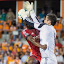 Houston Dynamo goalkeeper Tally Hall, right, knocks the ball away from Toronto FC defender Doneil Henry as they collide during the first half of a a Major League Soccer game on Saturday, June 22, 2013, at BBVA Compass Stadium in Houston. Dynamo player at bottom is unidentified. (AP Photo/Houston Chronicle, Smiley N. Pool)