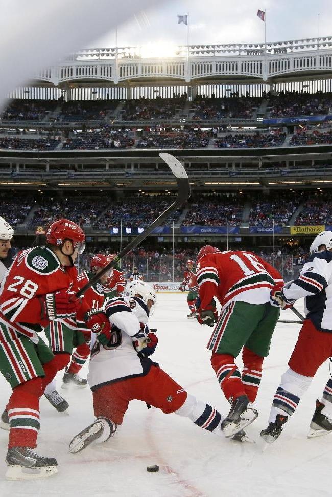 The puck slides beneath the legs of New York Rangers center Dominic Moore (28) as New Jersey Devils defenseman Anton Volchenkov (28) defends in the third period of an NHL outdoor hockey game at Yankee Stadium in New York, Sunday, Jan. 26, 2014. The Rangers won 7-3