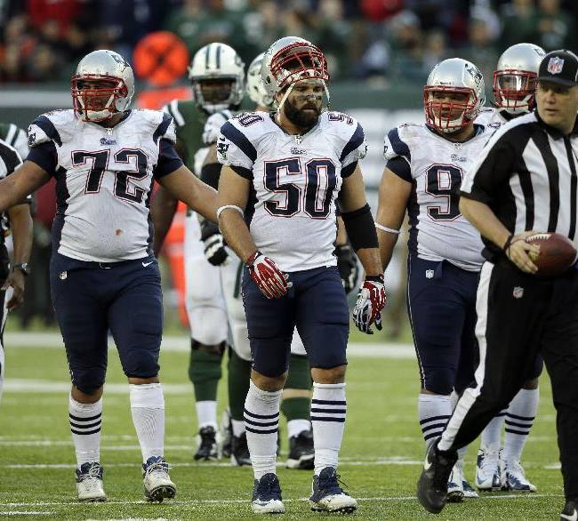 In this photo taken Sunday, Oct. 20, 2013, New England Patriots' Joe Vellano (72), Rob Ninkovich (50) and Chris Jones (94) watch as an official advances the ball after Jones was called for an unsportsmanlike penalty during overtime of an NFL football game against the New York Jets in East Rutherford, N.J. Jones was called for the penalty after pushing a teammate forward to try to block a Jets field goal, a new NFL rule. The Jets won the game 30-27 in overtime