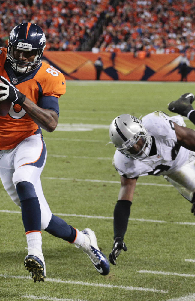 Denver Broncos tight end Julius Thomas (80) gets by Oakland Raiders outside linebacker Kevin Burnett (94) on his way to a touchdown in the second quarter of an NFL football game, Monday, Sept. 23, 2013, in Denver