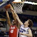 New Mexico's Kendall Williams, left, is blocked on his way to the basket by Saint Louis' Rob Loe during the first half of an NCAA college basketball game, Monday, Dec. 31, 2012, in St. Louis. (AP Photo/Jeff Roberson)