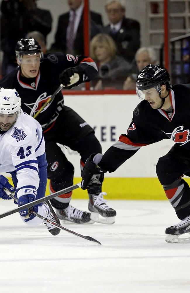 Carolina Hurricanes' Brett Sutter (42) and Alexander Semin, rear, of Russia, chase the puck against Toronto Maple Leafs' Nazem Kadri (43) and Joffrey Lupul (19) during the first period of an NHL hockey game in Raleigh, N.C., Thursday, Jan. 9, 2014