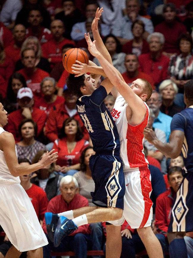 Charleston Southern's Matt Kennedy, second from left, tries to shoot over New Mexico's Alex Kirk in the first half of an NCAA basketball game Sunday, Nov. 17, 2013, in Albuquerque, N.M.  New Mexico won 109-93