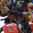 Miami Heat's LeBron James (6) looks to pass under the pressure of Washington Wizards defenders Martell Webster (9) and Drew Gooden (90) during the first half of an NBA basketball game in Miami, Monday, March 10, 2014. (AP Photo/J Pat Carter)