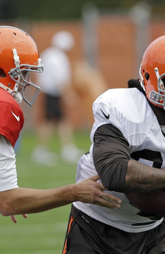 Cleveland Browns running back Trent Richardson takes a handoff from quarterback Brian Hoyer (6) during NFL football practice at the team's training facility in Berea, Ohio, Wednesday, Sept. 18, 2013. The Browns have traded Richardson to the Indianapolis Colts on Wednesday, a stunning move just two games into this season and only one year after drafting him in the first round