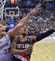 Portland Trail Blazers guard Damian Lillard, right, puts up a shot as Los Angeles Clippers forward Blake Griffin defends during the first half of an NBA basketball game, Wednesday, Feb. 12, 2014, in Los Angeles. (AP Photo/Mark J. Terrill)