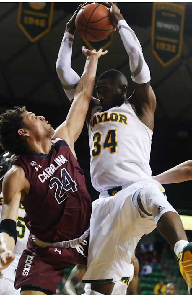 Michael Carrera (24), left, reaches for a rebound pulled down by Baylor's Cory Jefferson (34), right, in the first half of an NCAA college basketball game, Tuesday, Nov. 12, 2013, in Waco, Texas