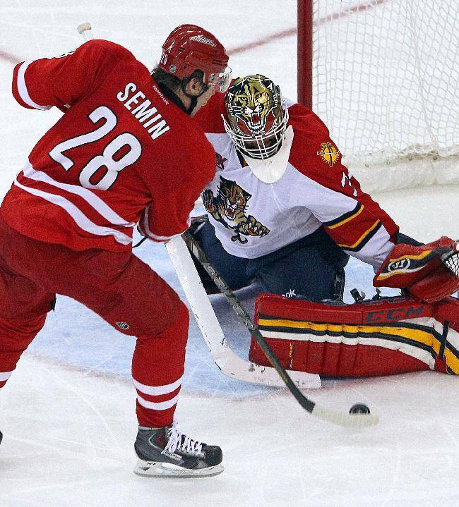 Carolina Hurricanes' Alexander Semin (28) of Russia, flips the puck over the pad of Florida Panthers goalie Tim Thomas (34) for his second goal of the game during the third period of an NHL hockey game in Raleigh, N.C., Saturday, Jan. 18, 2014. Hurricanes won 3-2