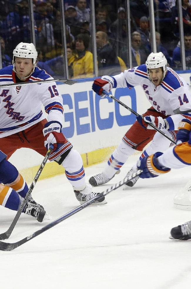 New York Islanders' Casey Cizikas (53) gets control of the puck from New York Rangers' Derek Dorsett (15) as teammate Thomas Hickey (14) falls to the ice during the first period of an NHL hockey game Tuesday, Oct. 29, 2013, in Uniondale, N.Y