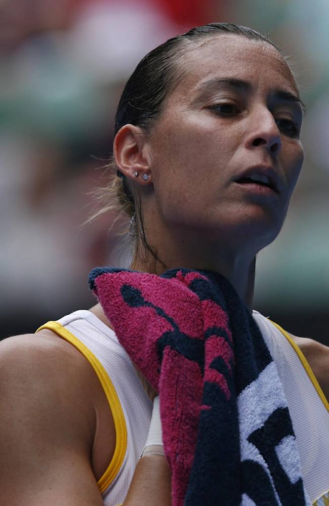 Flavia Pennetta of Italy wipes the sweat from her face as she plays Angelique Kerber of Germany during their fourth round match at the Australian Open tennis championship in Melbourne, Australia, Sunday, Jan. 19, 2014