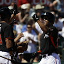 Miami Marlins' Giancarlo Stanton, right, high-fives teammate Garrett Jones as he crosses home plate after hitting a home run in the fourth inning of an exhibition spring training baseball game against the Detroit Tigers, Sunday, March 9, 2014, in Jupiter,