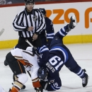 Winnipeg Jets' Jim Slater (19) is upended at a face-off with Anaheim Ducks' Ryan Kesler (17) during the third period of their NHL hockey game in Winnipeg, Manitoba, Canada on Saturday, Dec. 13, 2014 The Associated Press