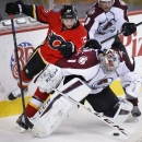 Colorado Avalanche goalie Semyon Varlamov, bottom, from Russia, is checked Calgary Flames' Sven Baertschi, from Switzerland, as Colorado's Jan Hejda, from the Czech Republic, looks on during the first period of an NHL hockey game, Thursday, Dec. 4, 2014 i