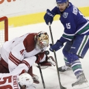 Phoenix Coyotes goaltender Mike Smith (41) makes a save against Vancouver Canucks' Brad Richardson (15) while being knocked over by teammate Antoine Vermette during third period NHL hockey action in Vancouver, British Columbia, on Friday Dec. 6, 2013 The