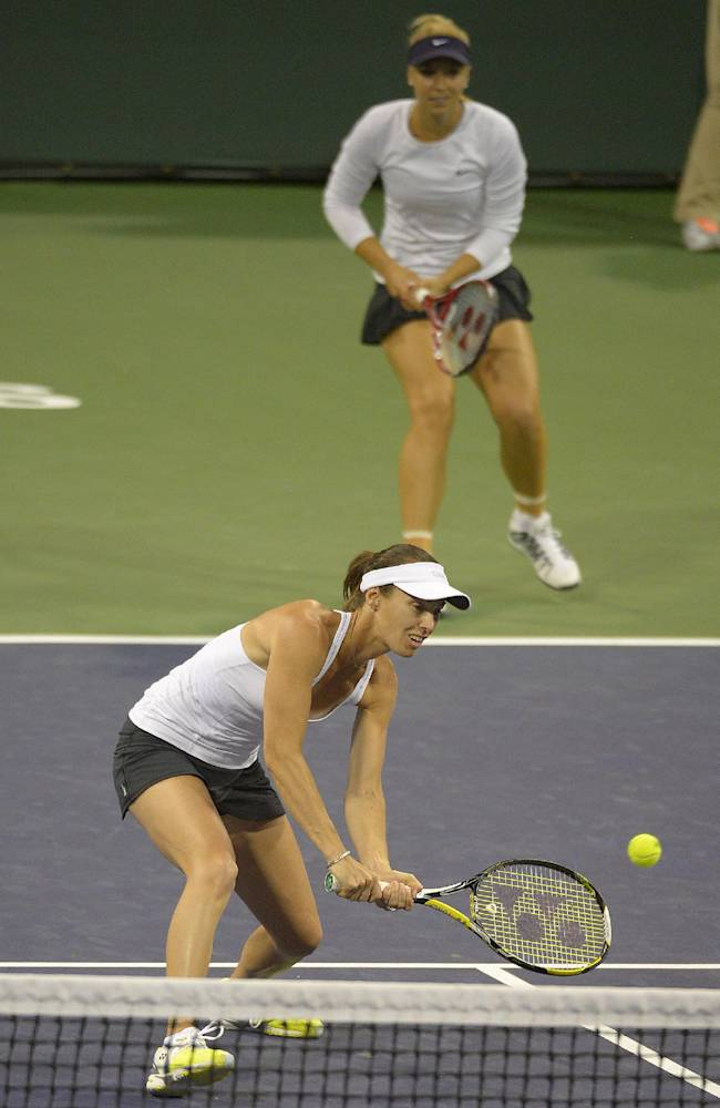 Martina Hingis, of Switzerland, foreground, returns a shot in front of her partner Sabine Lisicki, of Germany, as they compete against Ashleigh Barty, of Australia, and Casey Dellacqua, of Australia, during a first round doubles match at the BNP Paribas Open tennis tournament, Thursday, March 6, 2014, in Indian Wells, Calif
