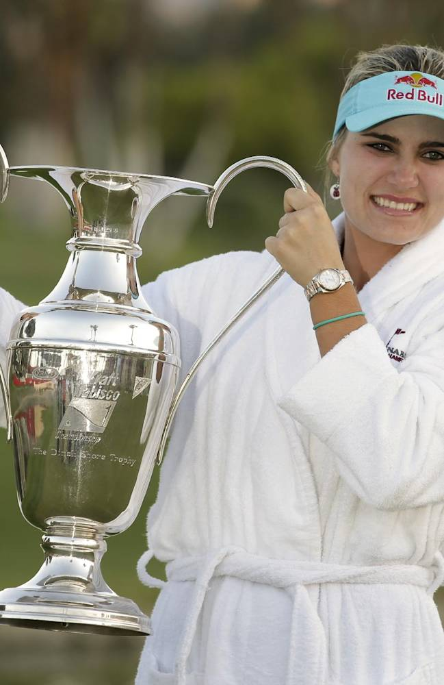 Lexi Thompson holds up the trophy after winning the Kraft Nabisco Championship golf tournament Sunday, April 6, 2014, in Rancho Mirage, Calif