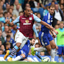 Aston Villa's Gabriel Agbonlahor, left, is fouled by Chelsea's Cesc Fabregas, centre, as he competes for the ball with Chelsea's Branislav Ivanovic, right, during their English Premier League soccer match against Aston Villa at Stamford Bridge, London, Sa