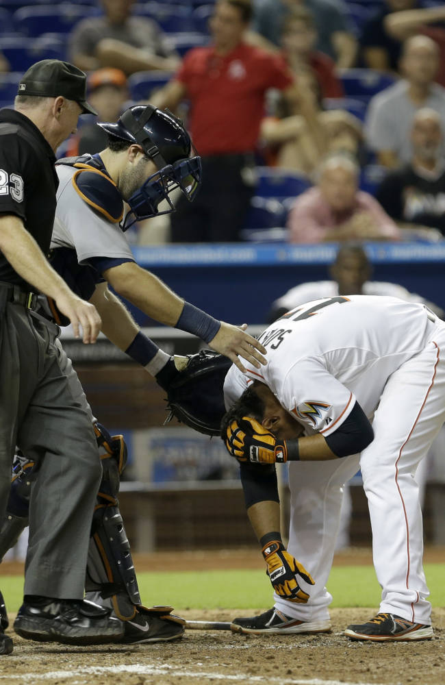 Miami Marlins' Donovan Solano, right, holds his head after he was hit by a pitch from Detroit Tigers reliever Evan Reed (57) in the tenth inning of an interleague baseball game on Saturday, Sept. 28, 2013, in Miami. Tigers' catcher Alex Avila, center, and home plate umpire Lance Barksdale (23) assist Solano. The Marlins won 2-1