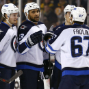 Winnipeg Jets' Dustin Byfuglien, second from left, is congratulated by Michael Frolik (67) and Jacob Trouba (8) after scoring against the Boston Bruins during the first period of an NHL hockey game in Boston, Friday, Nov. 28, 2014 The Associated Press