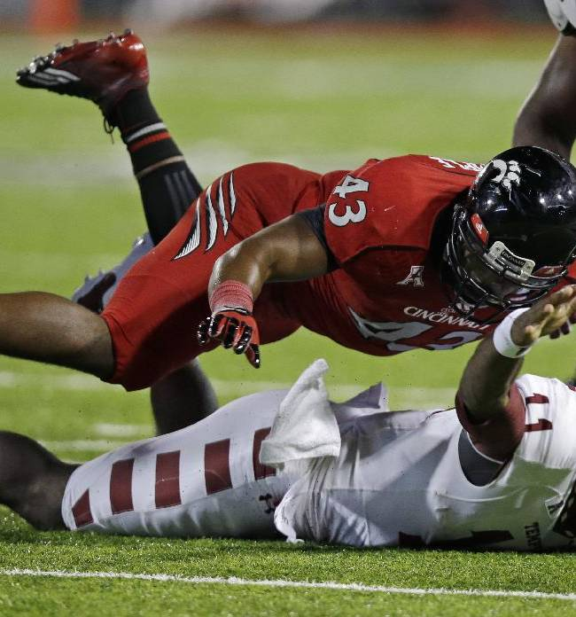 Temple quarterback P.J. Walker (11) fumbles the ball as he is tackled by Cincinnati linebacker Nick Temple (43) in the second half of an NCAA college football game, Friday, Oct. 11, 2013, in Cincinnati. Cincinnati recovered the fumble
