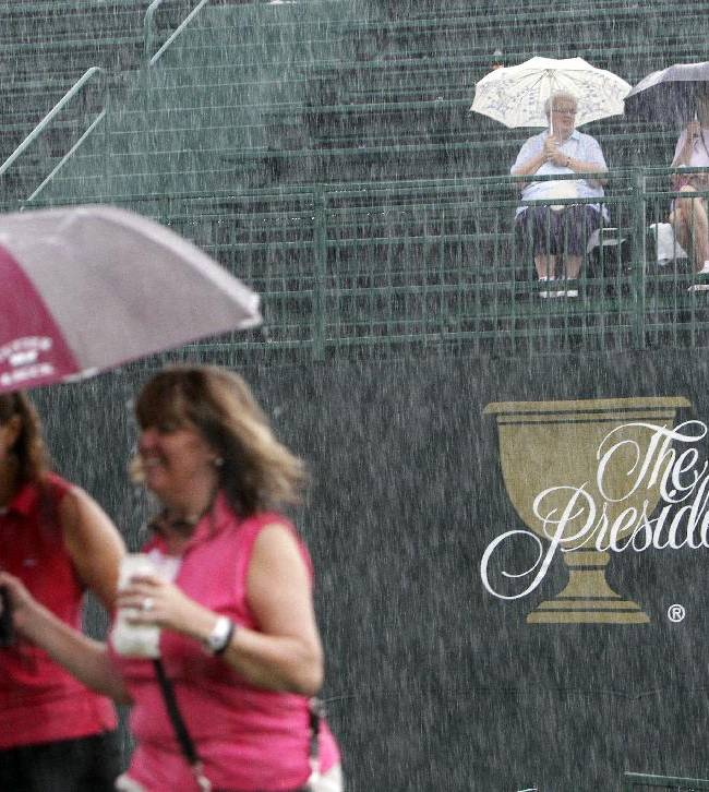 Fans brave the rain during a weather delay at the Presidents Cup golf tournament at Muirfield Village Golf Club Friday, Oct. 4, 2013, in Dublin, Ohio