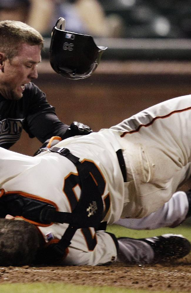 In this May 25, 2011, file photo, Florida Marlins' Scott Cousins, top, collides with San Francisco Giants catcher Buster Posey on a fly ball hit by Marlins' Emilio Bonifacio during the 12th inning of a baseball game in San Francisco. Posey wants all players protected from hard collisions at home plate and serious injuries, baserunners and catchers alike, whether Major League Baseball implements a new rule banning home-plate collisions in time for the 2014 season
