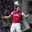 Arsenal's Alex Oxlade-Chamberlain, front, jumps for the ball against Everton's Sylvain Distin during their English Premier League soccer match at Goodison Park Stadium, Liverpool, England, Sunday April 6, 2014
