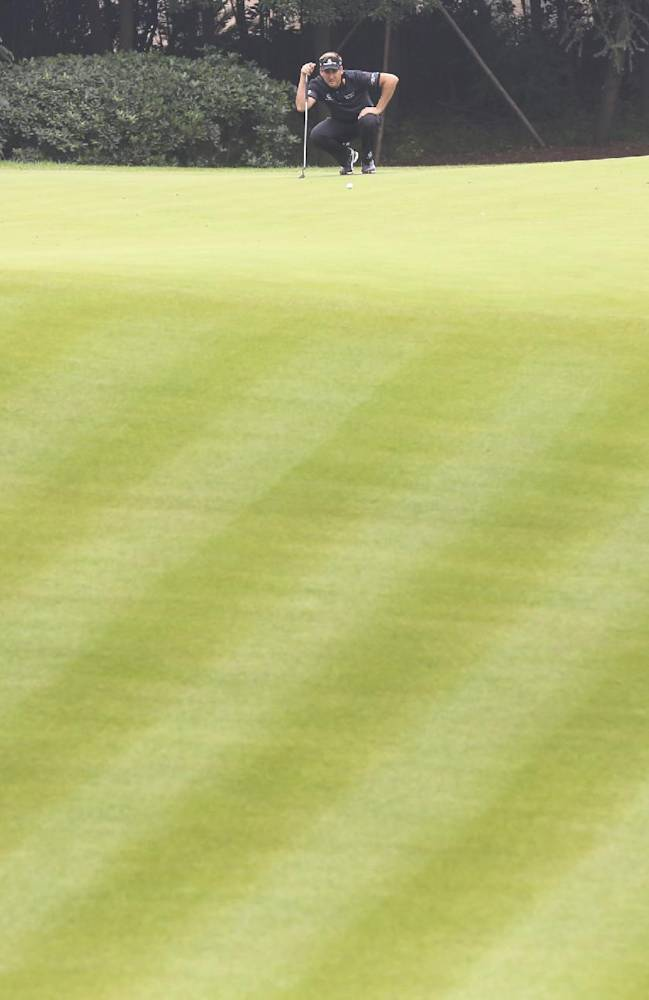 Early leader and defending champion Ian Poulter of England lines up on the 7th green during the final round of the HSBC Champions golf tournament at the Sheshan International Golf Club in Shanghai, China, Sunday, Nov. 3, 2013