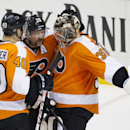 Philadelphia Flyers' Steve Mason, right, talks with Scott Hartnell, center, and Vincent Lecavalier, left, as they celebrate after an NHL hockey game against the Winnipeg Jets, Friday, Nov. 29, 2013, in Philadelphia. The Flyers won 2-1 The Associated Press