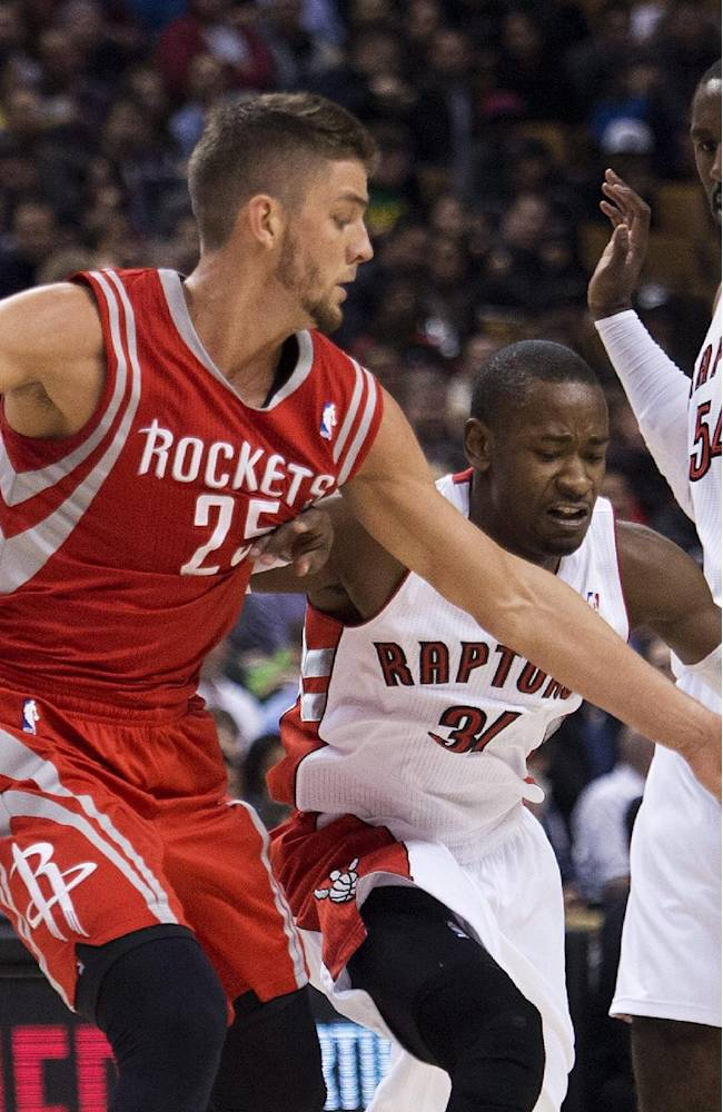 Toronto Raptors forward Terrence Ross, center, battles for the loose ball against Houston Rockets forward Chandler Parsons, left, as, Raptors forward Patrick Patterson, right, looks on during first-half NBA basketball action in Toronto, Wednesday, April 2, 2014