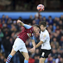 Aston Villa's Tom Cleverley, left, and Bournemouth's Harry Arter battle for the ball in the air during the English FA Cup fourth round soccer match at Villa Park, Birmingham, England, Sunday Jan. 25, 2015