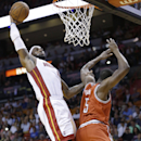 Miami Heat forward LeBron James, left, dunks against Milwaukee Bucks forward Ekpe Udoh (5) during the first half of an NBA basketball game on Wednesday, April 2, 2014, in Miami The Associated Press