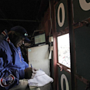 In this April 10, 2014 photo, scoreboard operator Darryl Wilson keeps up with the game as he watches from inside Wrigley Field's iconic scoreboard as during a baseball game between Pittsburgh Pirates and Chicago Cubs, in Chicago. Wilson mans the two top f