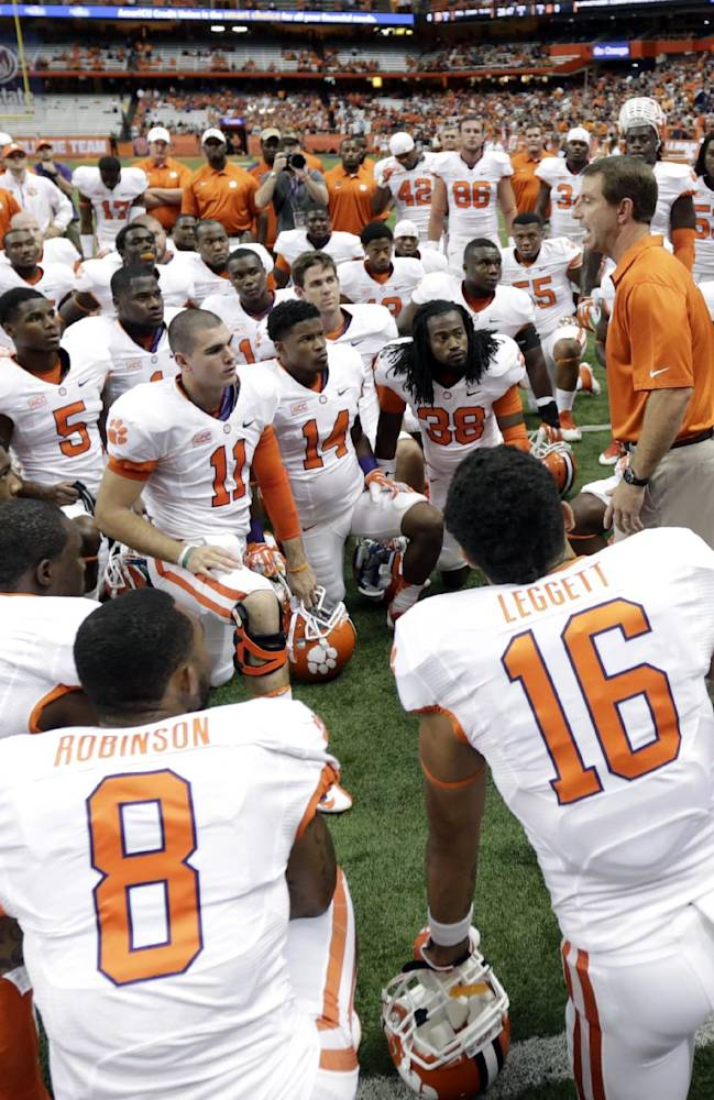 Clemson head coach Dabo Swinney, center right talks to his players before an NCAA college football game against Syracuse on Saturday, Oct. 5, 2013, in Syracuse, N.Y