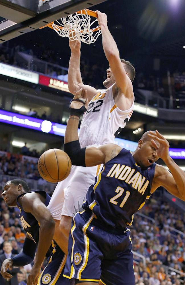 Phoenix Suns' Miles Plumlee (22) dunks as he powers past Indiana Pacers' David West (21) and Ian Mahinmi, of France, left, during the second half of an NBA basketball game Wednesday, Jan. 22, 2014, in Phoenix.  The Suns defeated the Pacers 124-100