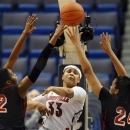 Louisville's Monique Reid, center, passes between St. John's Amber Thompson, left, and Mary Nwachukwu in the first half of an NCAA college basketball game in the quarterfinals of the Big East women's tournament in Hartford, Conn in Hartford, Conn., Sunday, March 10, 2013. (AP Photo/Jessica Hill)