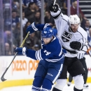 Toronto Maple Leafs defenseman Morgan Rielly (44) battles for the puck against Los Angeles Kings forward Dwight King (74) during first-period NHL hockey game action in Toronto, Sunday, Dec. 14, 2014 The Associated Press