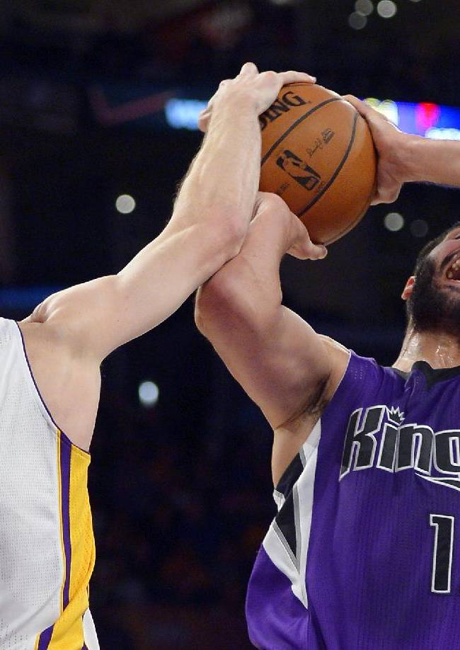 Los Angeles Lakers guard Steve Blake, left, blocks the shot of Sacramento Kings guard Greivis Vasquez, of Venezuela, during the second half of an NBA basketball game Sunday, Nov. 24, 2013, in Los Angeles