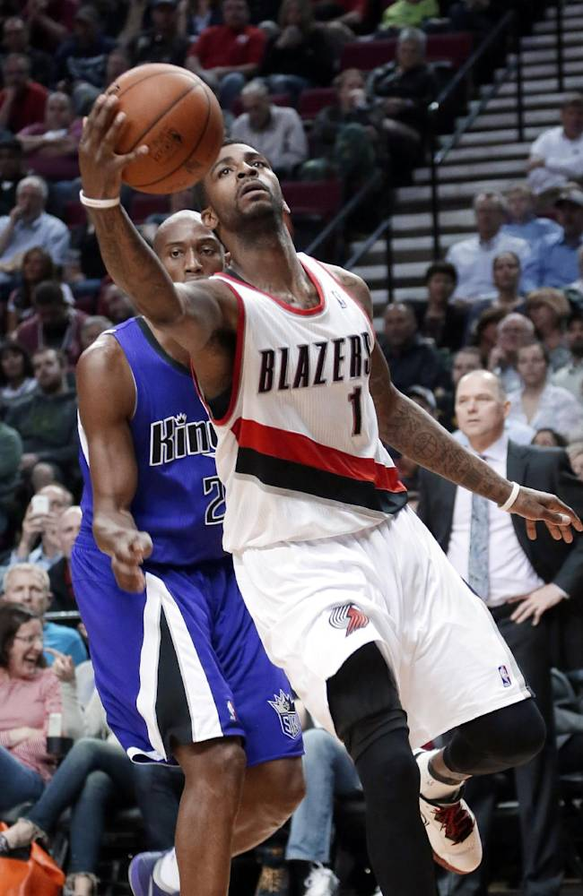 Portland Trail Blazers forward Dorell Wright, right, drives to the basket past Sacramento Kings forward Travis Outlaw during the second half of an NBA basketball game in Portland, Ore., Wednesday, April 9, 2014. Wright later sank a 3-point shot with just seconds to go to give the Trail Blazers the lead on the way to a 100-99 win
