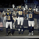 In this Nov. 30, 2014, file photo, St. Louis Rams players, from left; Stedman Bailey (12), Tavon Austin (11), Jared Cook, (89) Chris Givens (13) and Kenny Britt (81) raise their arms in awareness of the events in Ferguson, Mo., as they walk onto the fiel