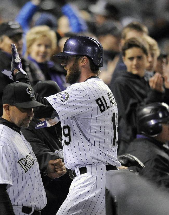 Colorado Rockies' Charlie Blackmon is congratulated by his teammates after scoring in the fifth inning of a baseball game against the Arizona Diamondbacks on Saturday, April 5, 2014, in Denver. Blackmon went 3-for-4, tying the Rockies' franchise record with nine hits in consecutive games