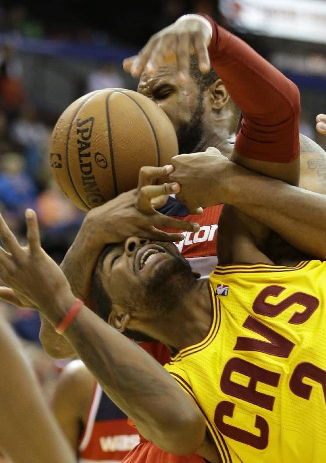 Cleveland Cavaliers point guard Kyrie Irving, bottom, fights for a rebound with Washington Wizards forward Trevor Booker in the second half of an NBA preseason basketball game on Wednesday, Oct. 23, 2013, in Cincinnati. Washington won 101-82