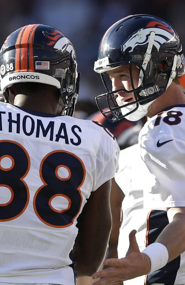 Denver Broncos quarterback Peyton Manning, right, greets Denver Broncos wide receiver Demaryius Thomas as he returns to the sidelines following his third touchdown reception in the second half of a NFL football game against the San Diego Chargers Sunday, Nov. 10, 2013, in San Diego
