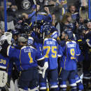 St. Louis Blues surround teammate Barret Jackman, center, after his game-winning goal against the Chicago Blackhawks during overtime in Game 2 of a first-round NHL hockey playoff series, Saturday, April 19, 2014, in St. Louis. (AP Photo/Bill Boyce)