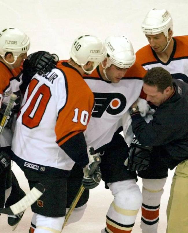 In this May 26,  2000, file photo, Philadelphia Flyers Eric Lindros, third from right, is assisted after getting hit in the first period of Game 7 of the nHL hockey Eastern Conference finals against the New Jersey Devils in Philadelphia.  Lindros was skating up the ice with the puck when Devils' Scott Stevens blind-sided him with an elbow. NHL Commissioner Gary Bettman declined comment on the impact of the NFL concussions lawsuit, but he said the league has been proactive for decades in addressing head injuries