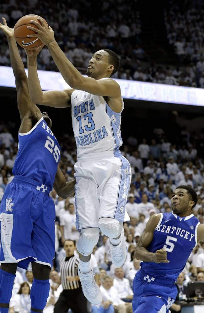 North Carolina's J.P. Tokoto (13) drives to the basket as Kentucky's Dominique Hawkins (25) and Andrew Harrison (5) defend during the first half of an NCAA college basketball game in Chapel Hill, N.C., Saturday, Dec. 14, 2013