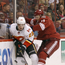Calgary Flames' Sean Monahan (23) plays the puck off the boards as he is hit by Arizona Coyotes' Martin Hanzal, of the Czech Republic, during the second period of an NHL game Saturday, Nov. 29, 2014 in Glendale, Ariz The Associated Press