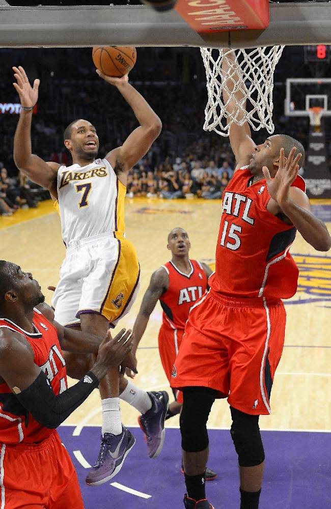 Los Angeles Lakers guard Xavier Henry, upper left, puts up a shot as Atlanta Hawks forward Paul Millsap, left, and Atlanta Hawks center Al Horford, of the Dominican Republic, defend during the second half of their NBA basketball game, Sunday, Nov. 3, 2013, in Los Angeles. The Lakers won 105-103