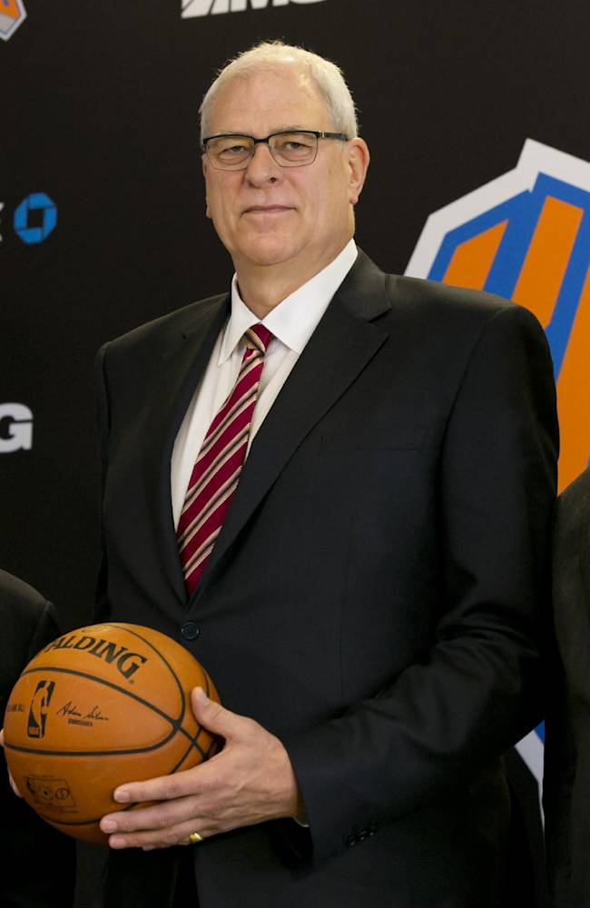 New York Knicks new team president Phil Jackson, center, poses for photos with team owner James Dolan, left, and general manager Steve Mills, during a news conference where he was introduced, at New York's Madison Square Garden, Tuesday, March 18, 2014
